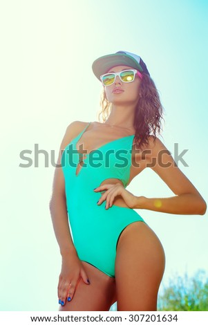 Slender sexy tanned girl in bikini posing over blue sky. Summer vacation. Beauty, fashion. - stock photo