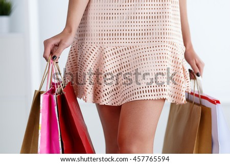 Slender walking legs of woman in dress holding colored paper bags. Retail business, beauty clothes stylist, urban colour, boutique and mall visiting occasion, pay for enjoyment, item delivery concept - stock photo