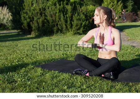 Slender woman is engaged in gymnastics for the body BODY AND STRETCH all muscles,she sits on the grass on a sunny put.beautiful girl sitting on the mat for fitness and meditates girl ,green grass - stock photo