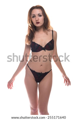 Slender young redheaded woman in red and black lingerie