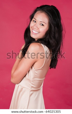 Slender young Singaporean Chinese woman in a cream colored dress