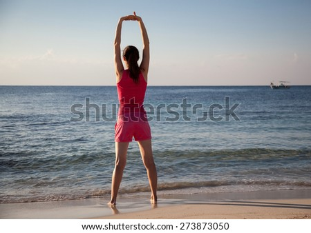 Slender young woman doing exercises on the sea coast at dawn - stock photo