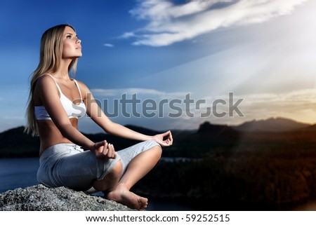 Slender young woman doing yoga exercise outdoors. - stock photo