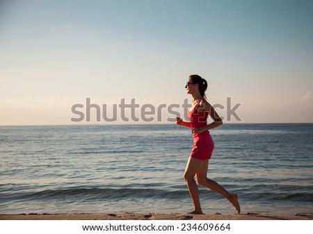 Slender young woman running along the seacoast - stock photo