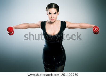 Slender young woman with beautiful athletic body doing exercises with dumbbells. Fitness, bodybuilding. Health care. - stock photo