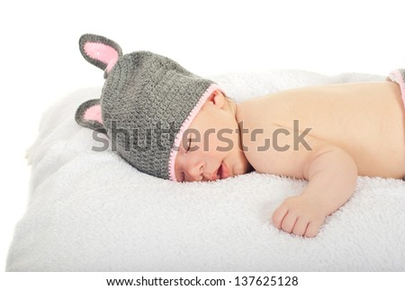 Slereping baby with knitted bunny cap isolated on white background