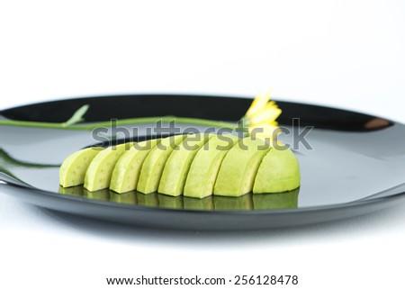 Slice avocado fruit on black dish - stock photo