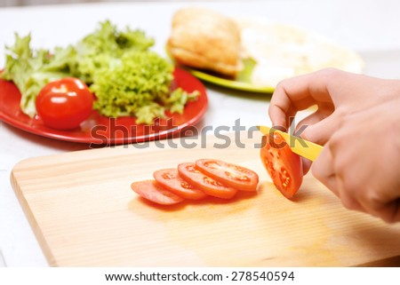 Slice by slice. Close up of man slicing tomatoes on wooden board in kitchen. - stock photo
