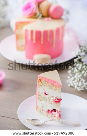 Slice of a biscuit cake with buttercream and raspberries inside, pink frosting and white chocolate ganache. Decorated with flowers and macaroons