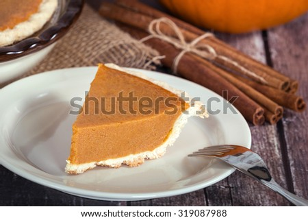 Slice of a pumpkin pie on wooden table. Pie and cinnamon sticks in the background.
