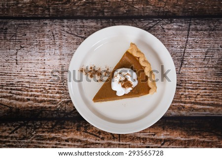Slice of a pumpkin pie on wooden vintage table - stock photo