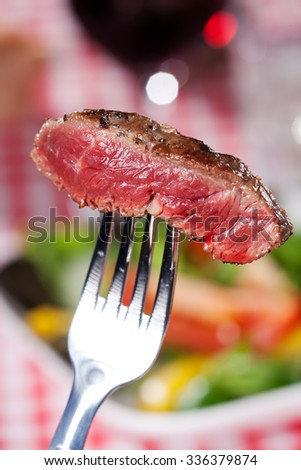 slice of a steak on a fork over salad  - stock photo