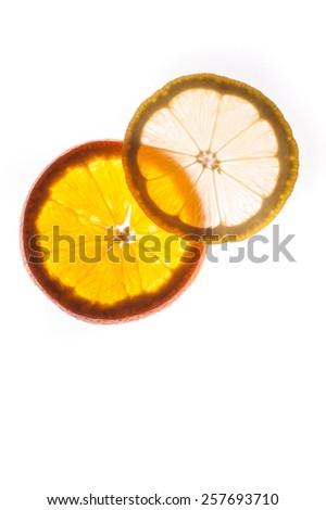 Slice of an orange and  lemon  isolated on white background back lit - stock photo