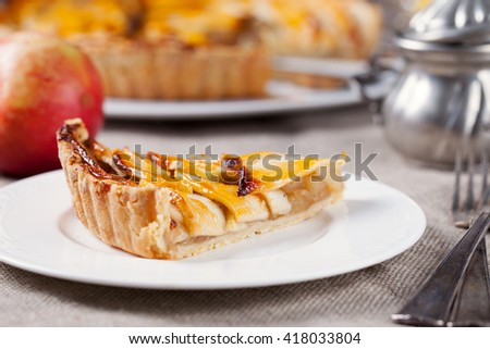 Slice of apple tart on a white plate Traditional holiday dessert Wooden rustic background - stock photo