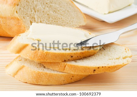 slice of baguette with butter on wooden board