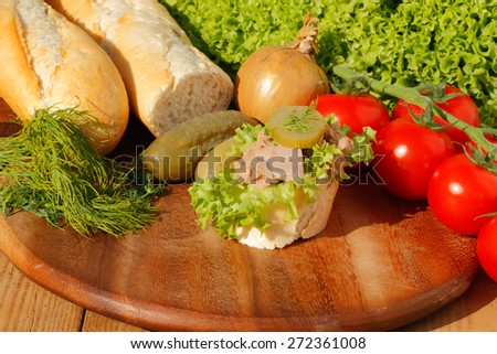 Slice of baguette with tuna fillet, garnished with lettuce, onion, tomato and pickles on a wooden board - stock photo