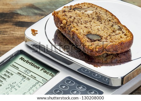 slice of banana bread with walnuts on diet scale displaying nutrition facts - a diet concept - stock photo