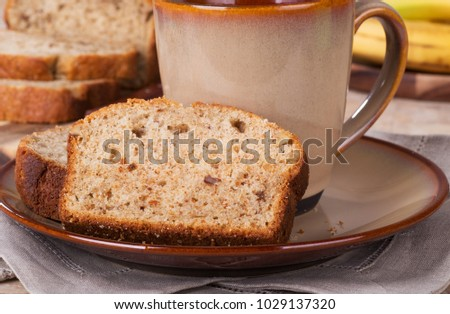 Slice of banana nut bread on a plate with a cup of coffee