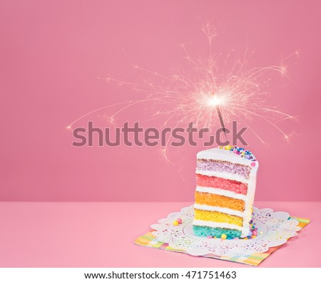 Slice of  birthday cake on a pink background with rainbow layers and sparkler.