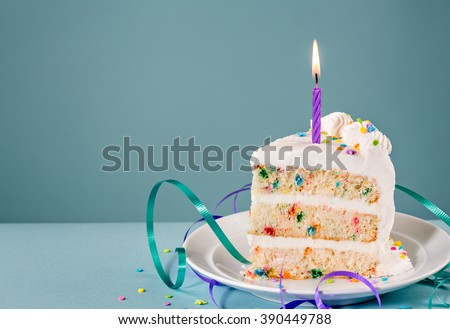 Slice of Birthday Cake with a lit candle and ribbons over a blue background. - stock photo