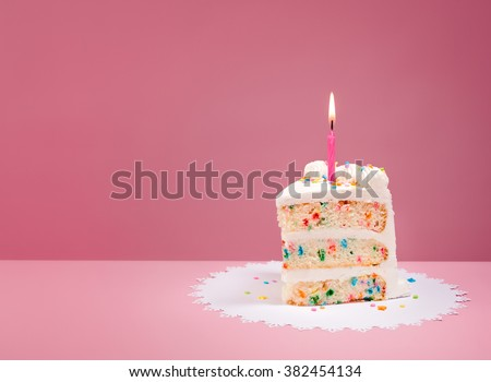 Slice of Birthday Cake with candle over a pink background. - stock photo