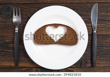 Slice of black bread with a cut in the shape of a heart on a plate. Next to the plate located cutlery. View from above. Conceptual photo.  - stock photo