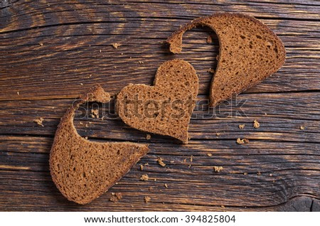 Slice of black bread with a cut in the shape of a heart on dark wooden background. View from above. Conceptual photo. - stock photo