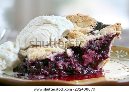 Slice of Blueberry Pie with vanilla ice cream on rustic wooden table - stock photo