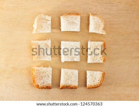 slice of bread chopped in pieces on wooden table
