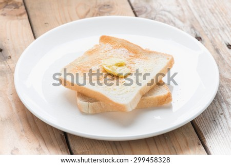 Slice of bread toast on a white plate.