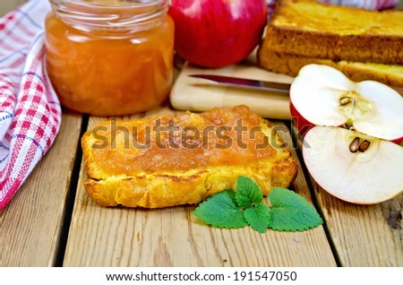 Slice of bread with apple jam and mint, a jar of marmalade, a napkin on the background of wooden boards - stock photo