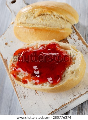 Slice of bread with strawberry jam on a wooden board. Selective focus