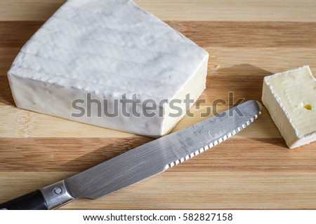 slice of brie cheese on wood cutting board close up