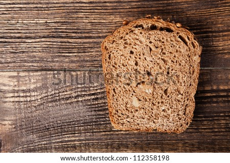 Slice of brown bread on a wooden table - stock photo