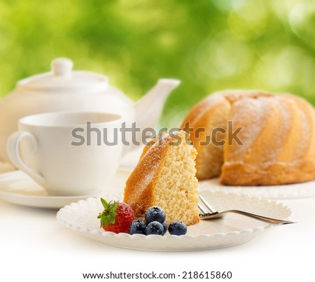 slice of cake and tea in a blurry green background - stock photo