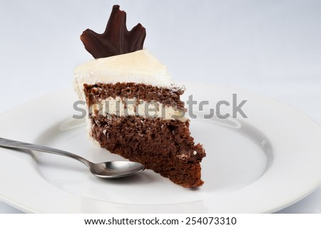 slice of cake with chocolate and whipped cream with white chocolate topping and with a piece of chocolate on top  and a spoon on a white plate on a white background