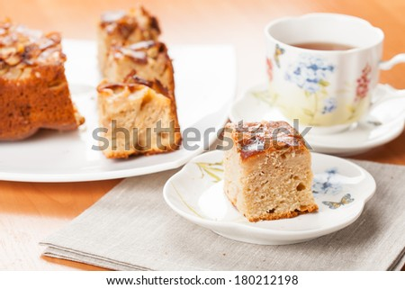 Slice of cake with tea served on a table - stock photo