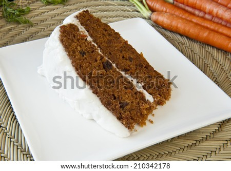 Slice of carrot cake with white frosting on a white plate - stock photo