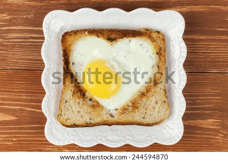 Slice of cereal toast bread with cut out heart shape full egg on white plate - stock photo