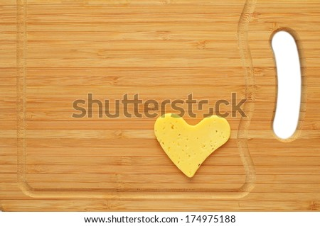 Slice of cheese in shape of heart on cutting board - stock photo