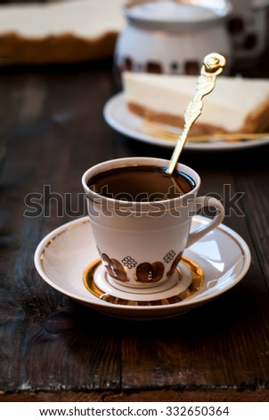 slice of cheesecake and a cup of black coffee for breakfast, a wooden background,