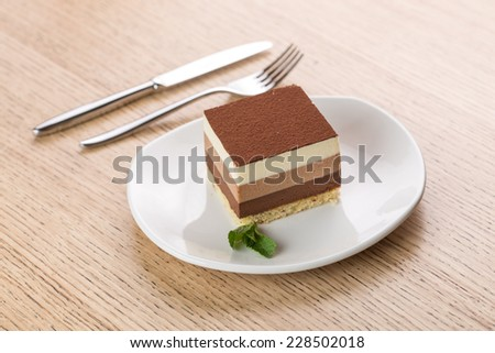 Slice of chocolate cake on round plate on wooden background - stock photo