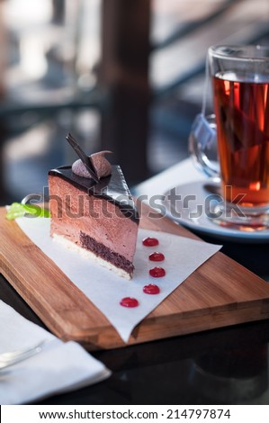 Slice of chocolate mousse cake with glass of hot black tea in outdoor restaurant at afternoon tea time. Typical regional cuisine, Cape Province, South Africa. Amber tones, selective focus, low key.