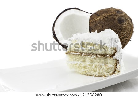 Slice of coconut cake with split coconut in background all isolated on white - stock photo