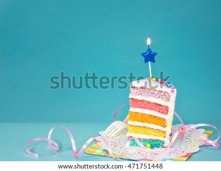 Slice of colorful birthday cake on blue