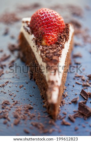 Slice of delicious chocolate and mascarpone cake with a fresh strawberry and roughly chopped chocolate flakes. Shallow DOF.