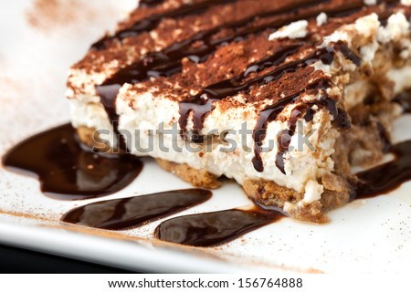 Slice of delicious tirimisu cake on a white plate garnished with cocoa power and drizzled chocolate sauce. - stock photo