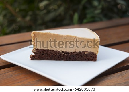 Slice of dulce de leche and chocolate brownie ice cream cake on a white plate outdoors