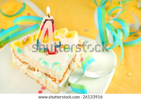 slice of fourth birthday cake with lit candle, confetti, and ribbon (shallow depth of field)