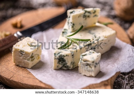 Slice of French Roquefort cheese with walnuts - stock photo